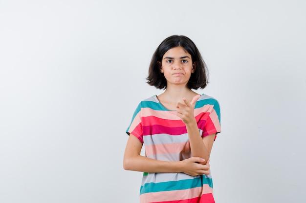 Klein meisje wijst terwijl ze de hand op de elleboog houdt in een t-shirt, spijkerbroek en er ontevreden uitziet, vooraanzicht.