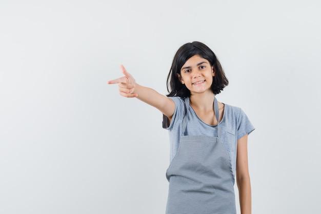 Klein meisje wijst weg in t-shirt, schort en kijkt zelfverzekerd. vooraanzicht.