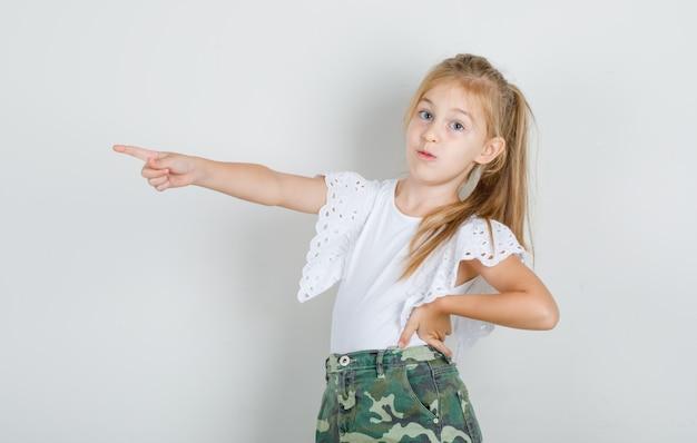 Klein meisje wijst weg met hand op taille in wit t-shirt