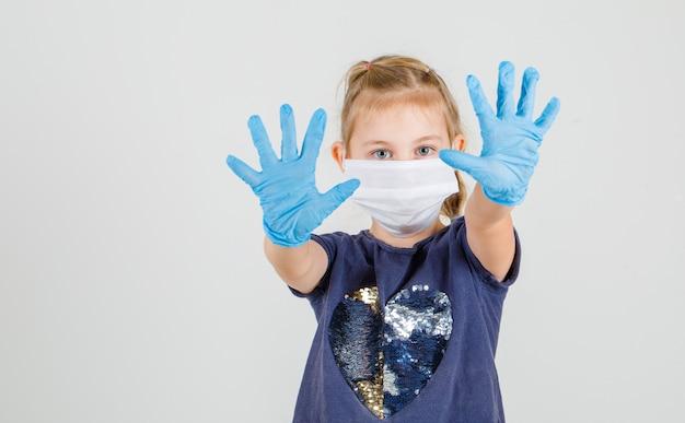 Klein meisje wijzend handen naar voren in t-shirt, handschoenen en masker en op zoek willable. vooraanzicht.