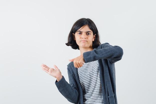 Klein meisje wijzend naar iets deed alsof ze werd vastgehouden in een t-shirt, jasje en peinzend keek.