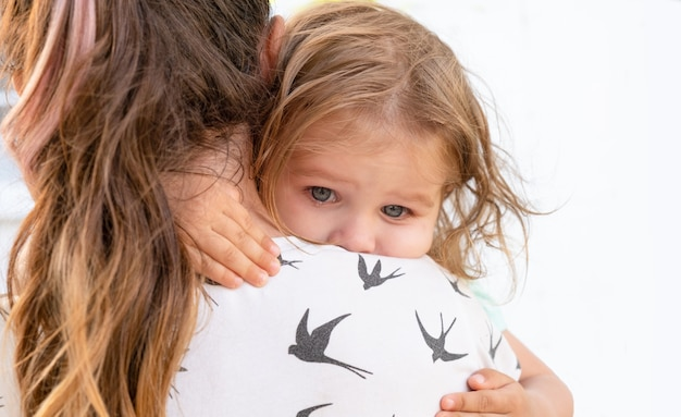 Klein meisje wordt geknuffeld door haar moeder