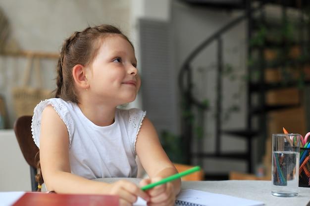 Klein meisje zit aan het bureau, schrijft in notitieblok, doet oefeningen thuis, klein kind handschrift bereidt huiswerk voor.