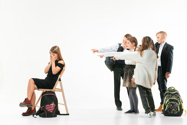 Klein meisje zit alleen op een stoel en lijdt aan pesterijen terwijl kinderen spotten. triest jonge schoolmeisje zittend op studio tegen een witte achtergrond.