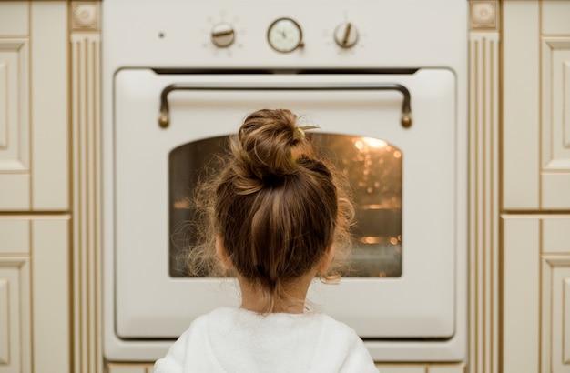 Klein meisje zit bij de oven en wacht op eten in de keuken.