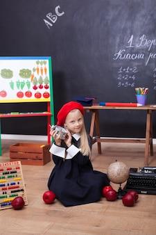 Klein meisje zit in een klaslokaal met wekker in haar handen