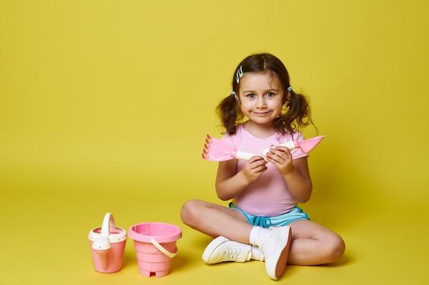 Klein meisje zit in een lotushouding in de buurt van roze strand speelgoed op een gele muur houdt een schop en hark glimlacht schattig poseren voor de camera geïsoleerd met kopie sapce