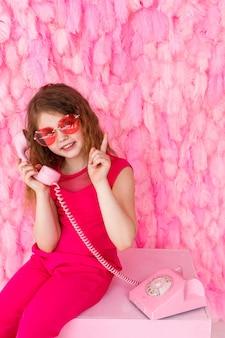 Klein meisje zit in een stijlvolle roze bril op roze met een roze telefoon en haar vinger omhoog