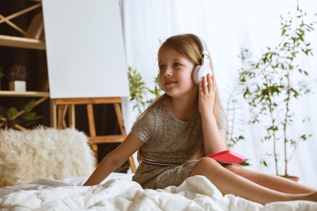Klein meisje zit in haar bed met grote koptelefoon luisteren naar favoriete muziek en genieten