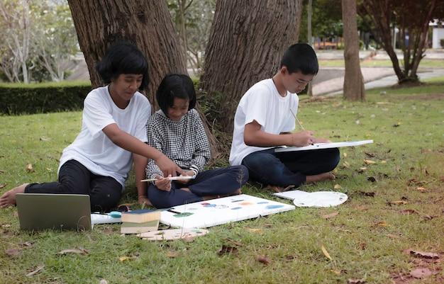 Klein meisje zit in het midden van jongere zus en haar broer. kleur schilderen op canvas. ze glimlachen met een gelukkig gevoel, doen samen activiteit in een park