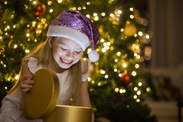 Klein meisje zit in ingerichte kerstkamer magische geschenkdoos met licht erin openen