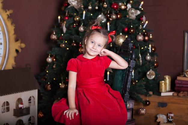 Klein meisje zit in livin kamer in de buurt van de kerstboom