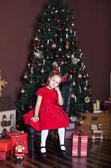 Klein meisje zit in livin kamer in de buurt van kerstboom en geschenken