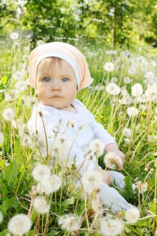 Klein meisje zit in paardebloemen