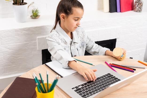 Klein meisje zit met een laptop aan de tafel en houdt een zandloper vast