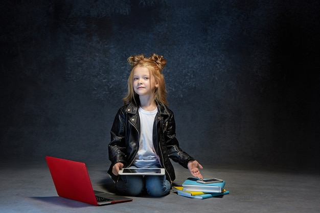 Klein meisje zit met laptop, tablet en telefoon in grijze studio