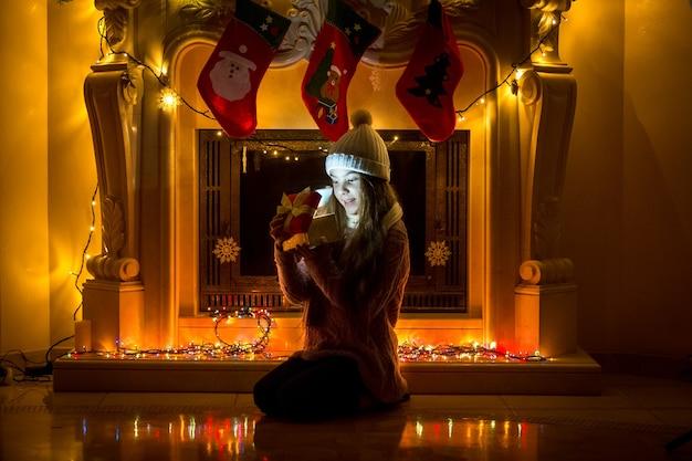 Klein meisje zit naast gedoofde open haard en kijkt naar kerstcadeaus