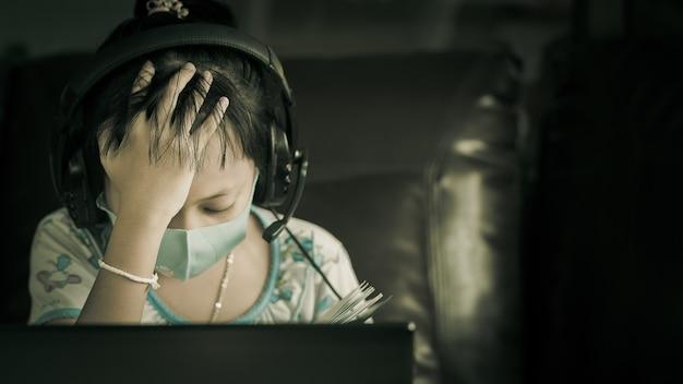Klein meisje zit online te studeren met stress totdat ze hoofdpijn heeft. concept van online leerprobleem