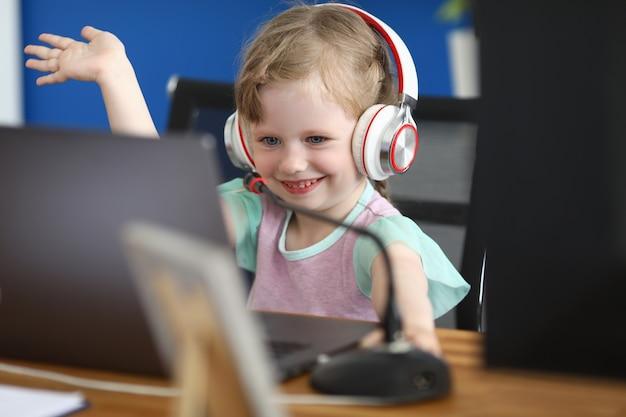 Klein meisje zit op de computer in hoofdtelefoons met microfoon glimlacht en zwaait met haar hand