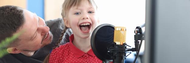 Klein meisje zit op de schoot van haar vader en zingt een lied in de creativiteit van kinderen van de microfoon