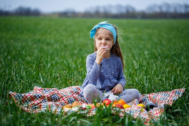 Klein meisje zit op de sprei en eet koekjes en marmelade, groen gras in het veld, zonnig lenteweer, glimlach en vreugde van het kind, blauwe lucht met wolken