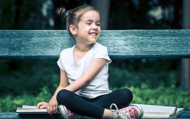 Klein meisje zit op een bankje en leest een boek