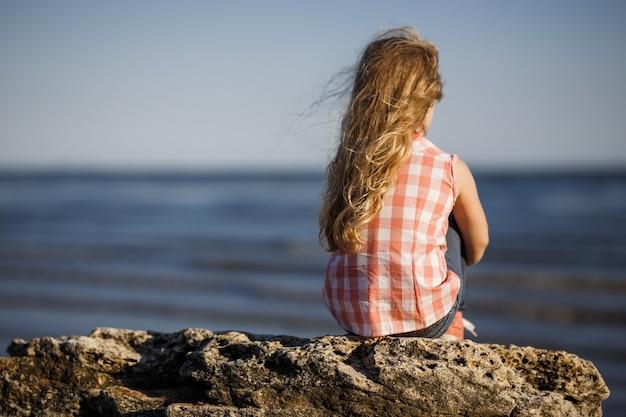 Klein meisje zit op een rotsachtige kust en kijkt naar de zee.