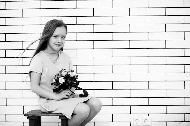 Klein meisje zit op een stoel en poseert op de camera