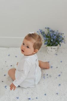 Klein meisje zit op een witte achtergrond met een vaas met vergeet-mij-nietjes