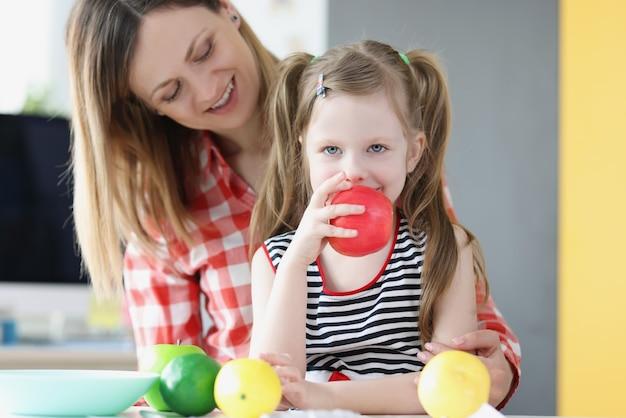 Klein meisje zit op haar moeders schoot en eet appel
