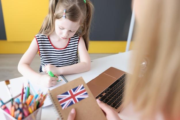Klein meisje zit op laptop met engelse studieboeken
