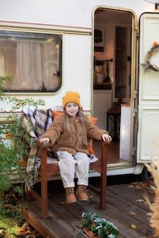 Klein meisje zit op veranda rv campinghuis met chrysant en pompoenen in de herfsttuin
