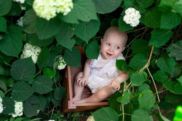 Klein meisje, zittend in bloemen in de zomer in een mooie jurk, bovenaanzicht