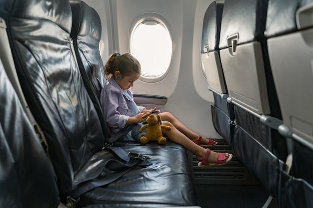 Klein meisje zittend in een stoel en genietend van haar telefoon tijdens een reis per vliegtuig
