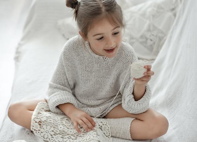 Klein meisje zittend op de bank en leren breien, home leisure concept.