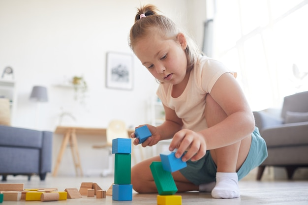 Klein meisje zittend op de bank en spelen met gekleurde blokken die ze thuis een piramide bouwt