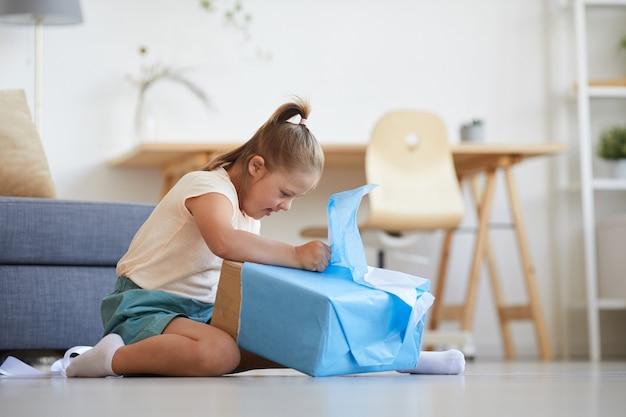 Klein meisje zittend op de vloer het blauwe inpakpapier scheuren ze opende haar cadeau in de kamer