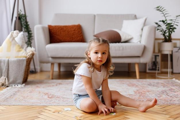 Klein meisje, zittend op de vloer in de woonkamer