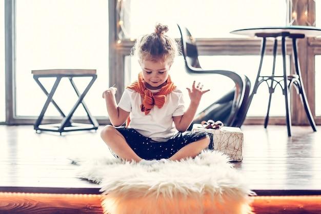 Klein meisje zittend op de vloer in een lichte kamer