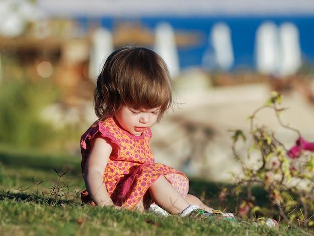 Klein meisje, zittend op het gras