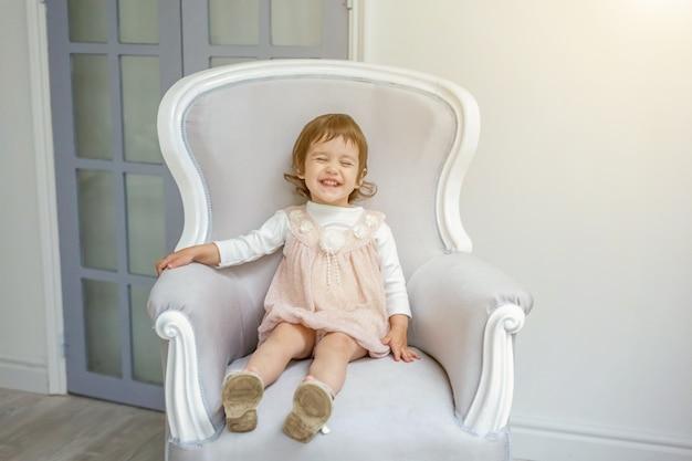 Klein meisje zittend op moderne stoel