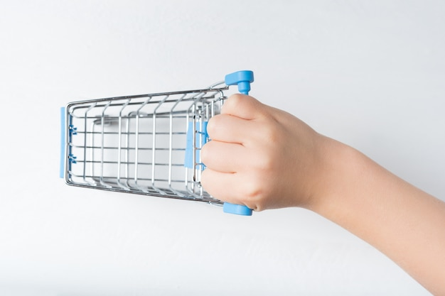Klein metalen winkelwagentje in een kinderhand