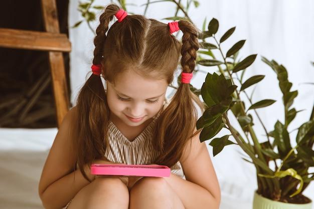Klein model zittend in haar kamer met smartphone en selfie maken of videochat met haar vrienden.