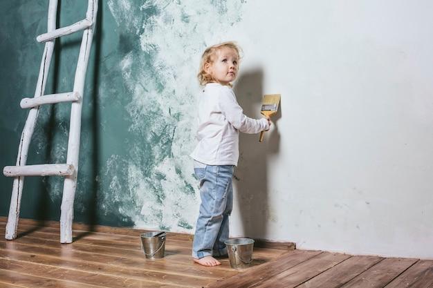 Klein mooi en gelukkig kind in spijkerbroek en op blote voeten verf de muur met penseel thuis