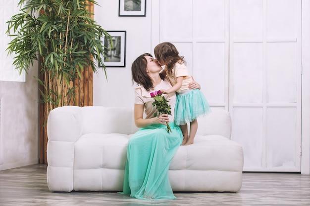 Klein mooi en schattig kindmeisje geeft bloemen aan de moeder in huis voor de vakantie