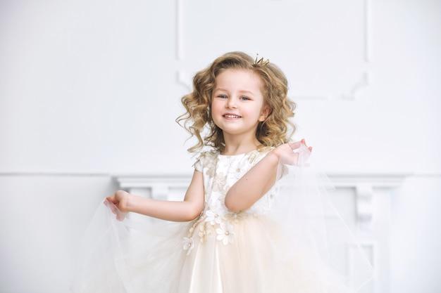 Klein mooi en schattig meisje in een modieuze feestjurk in een wit interieur