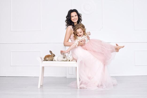 Klein mooi en schattig meisje in een modieuze feestjurk met dierenkonijnen