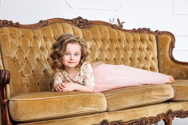 Klein mooi en schattig meisje in een modieuze feestjurk met op een luxe vintage bank