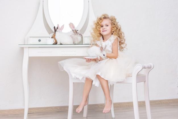 Klein mooi en schattig meisje in een trendy feestjurk met dierenkonijn in ligt op de vloer