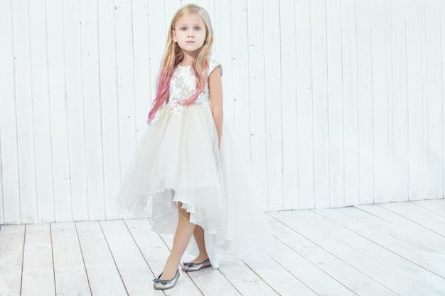 Klein mooi kind meisje in mooie jurk op witte houten achtergrond